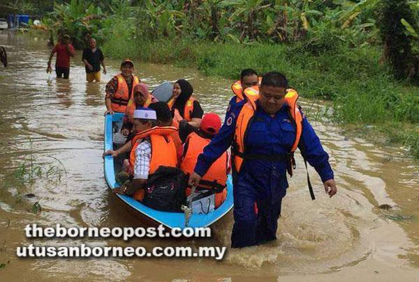 Beberapa anggota JPBN Sarawak membantu memindahkan mangsa banjir ke kawasan selamat.