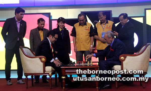 Mohd Asfia (duduk kanan) menggerakkan buah catur sambil disaksikan Chong (duduk kiri) semasa gimik perasmian Pertandingan Catur Antarabangsa 2018 turut disaksikan (dari kanan) Dr Rauf, Datuk Sebastian Ting, Len dan Violet Yong.