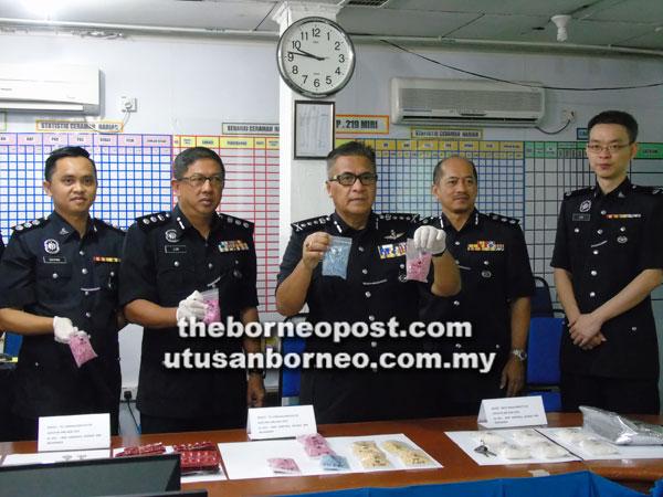 Amer (tiga kanan) menunjukkan bungkusan berisi pil-pil dipercayai dadah yang berjaya dirampas dalam serbuan di sebuah rumah.