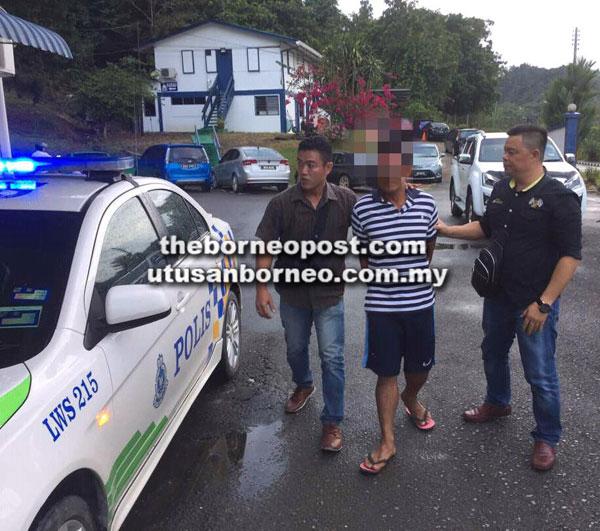Suspek diiringi anggota polis ke Balai Polis Lawas, kelmarin.