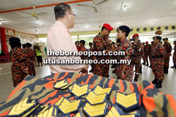 Nor Hisyam ngelekat tanda pangkat sarjan ba lengan siku kadet Bomba di Kem Santubong kemari.