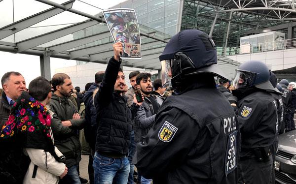 Polis berkawal di hadapan penunjuk perasaan yang membawa plakad menunjukkan mayat dan tulisan 'Turki mengebom orang awam' di lapangan terbang Duesseldorf kelmarin. — Gambar AFP