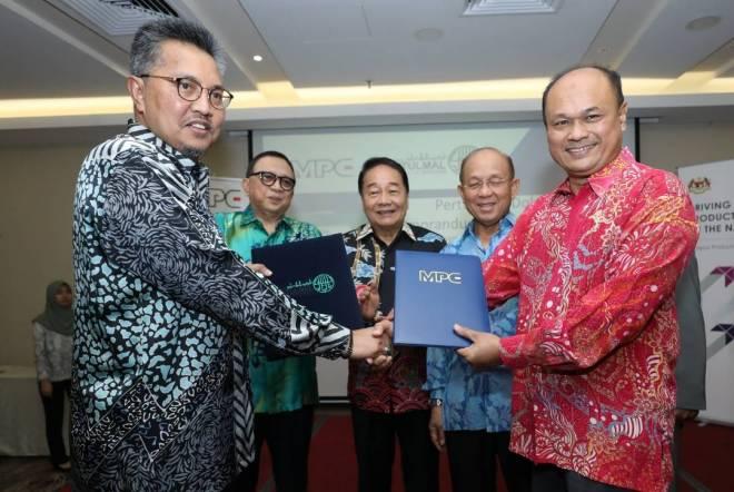 Shibli (kiri) bertukar dokumen MoU dengan Tengku Azmi sambil disaksikan Wong, Karim dan Azman.