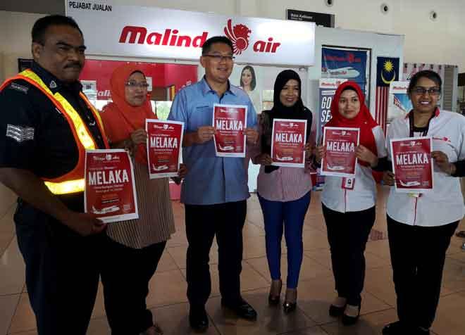 Lim (tiga kiri) menunjukkan poster pembukaan laluan baharu dari Medan Indonesia ke Melaka menggunakan Lapangan Terbang Antarabangsa Melaka (LTAM) di Batu Berendam pada sidang akhbar semalam. — Gambar Bernama