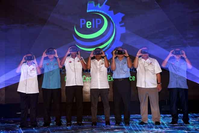 Mohamed Khaled (tengah), Pengarah Urusan Serba Dinamik Holdings Berhad Datuk Dr Ir Mohd Abdul Karim Abdullah (tiga, kanan) dan Pengarah Urusan Perisind Samudera Sdn Bhd Datuk Mohd Shafiee Mohd Sanip (dua, kanan) menggunakan Virtual Reality Box (VR-Box) sebagai gimik Pecah Tanah Pengerang Eco Industrial Park (PeIP) di Pengerang semalam. — Gambar Bernama
