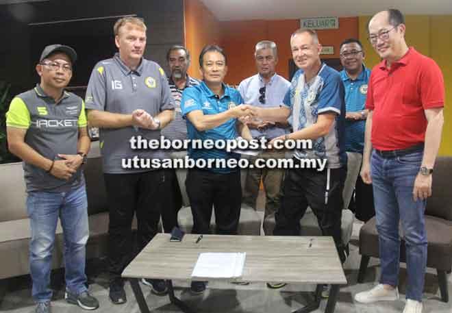 Posa (tiga kiri) dan Tony bertukar dokumen pada majlis menandatangani MoU di Stadium Negeri, Petra Jaya di Kuching petang kelmarin.