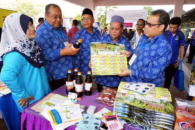 Abdul Fattah (kanan) melihat produk jualan anggota koperasi selepas merasmikan Majlis Persidangan ANGKASA Negeri Kedah di MRSM Merbok, semalam. — Gambar Bernama