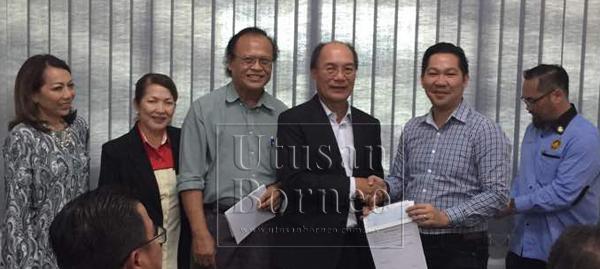 Gerawat menyampaikan cek kepada Petrus Lasong (dua kanan) mewakili gereja BEM on The Rock dan Persatuan Lun Bawang Sarawak.