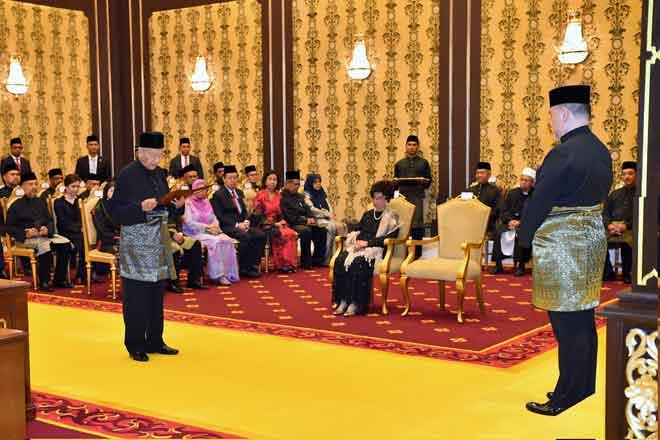 Tun Dr Mahathir membaca lafaz Surat Cara Pelantikan dan Mengangkat Sumpah Jawatan dan Setia Serta Sumpah Simpan Rahsia di hadapan Yang di-Pertuan Agong Sultan Muhammad V di Istana Negara, malam tadi. — Gambar Bernama