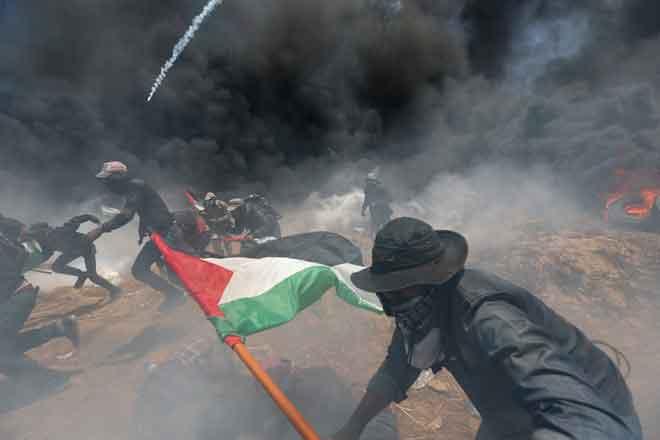 Pembantah Palestin melarikan diri dari gas pemedih mata ketika membantah pembukaan kedutaan AS di Baitulmuqaddis, di selatan Semenanjung Gaza kelmarin. — Gambar Reuters