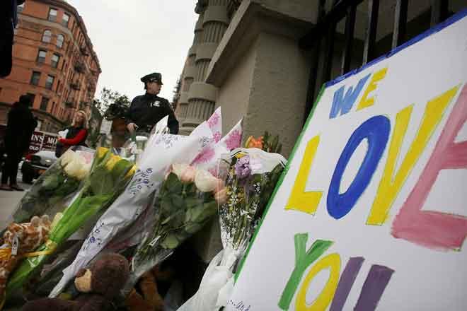 Gambar fail 26 Oktober, 2012 menunjukkan bunga dan pesanan ditinggalkan di hadapan bangunan di mana dua                      kanak-kanak ditikam hingga mati oleh pengasuh mereka di apartmen Upper West Side di New York. — Gambar AFP