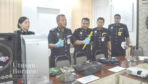 MOHD Azhar (dua kiri) menunjukkan barang kes jenayah yang dilaporkan berlaku di sekitar Sandakan.