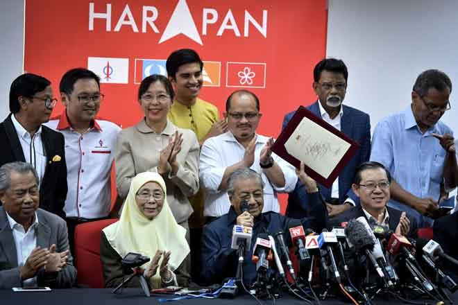 Tun Dr Mahathir Mohamad (duduk dua kanan) nerang ngagai pemberita pengudah bechairmanka Aum Presiden Pakatan Harapan Kemari. Bela bisi dipeda bala ketuai Muhyiddin (duduk kiba), Dr Wan Azizah (dua kiba), Lim Guan Eng (duduk kanan), Chong (bediri dua kiba) enggau bala bukai. — Gambar Bernama