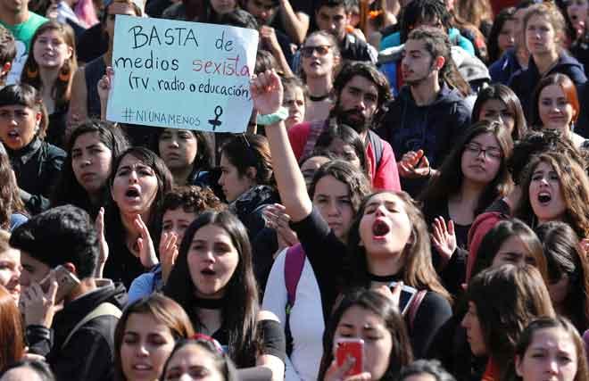 Penunjuk perasaan membawa sepanduk dan melaungkan slogan semasa perarakan dianjurkan oleh pelajar untuk membantah penderaan dan gangguan seksual terhadap wanita di Santiago, Chile kelmarin. — Gambar Reuters/AFP