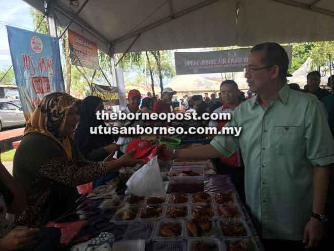 Fadillah melawat gerai jualan sambil berbual mesra dengan peniaga di Bazar Ramadan Sukma Ria di Kuching, semalam.