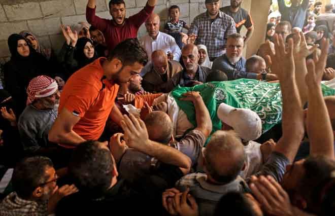 Penduduk Palestin mengusung jenazah Nasser Ghorab, 51, semasa upacara pengebumiannya di kem pelarian al-Nusirat di tengah semenanjung Gaza kelmarin selepas beliau terbunuh sehari sebelumnya dalam pertempuran dengan tentera Israel di sempadan Gaza. — Gambar AFP