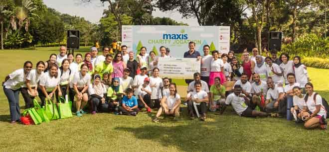 Ketua Pegawai Eksekutif Maxis Robert Nason (tengah kanan) menyampaikan cek kepada Chua (tengah kiri) di mana Maxis berjaya mengumpul dana lebih RM60,000 untuk NKF.