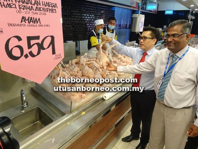 Stanley (dua kanan) memeriksa tanda dan harga ayam yang dijual di Mydin Petra Jaya, semalam. Turut kelihatan Pengurus Cawangan Mydin Rethnasamy Naidu Krishnan (kanan).