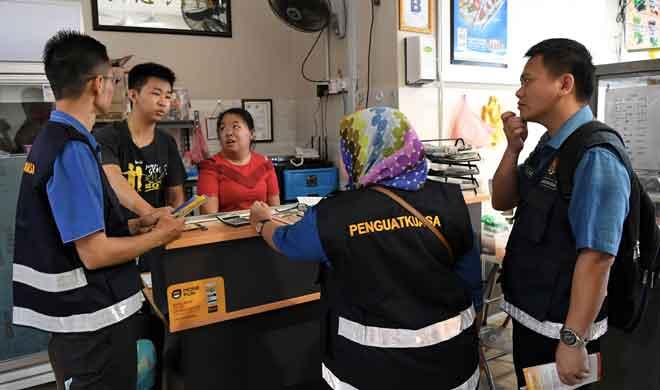 Pegawai penguat kuasa dari Jabatan Tenaga Kerja Sabah melakukan operasi gaji di kedai-kedai Inanam semalam. — Gambar Bernama