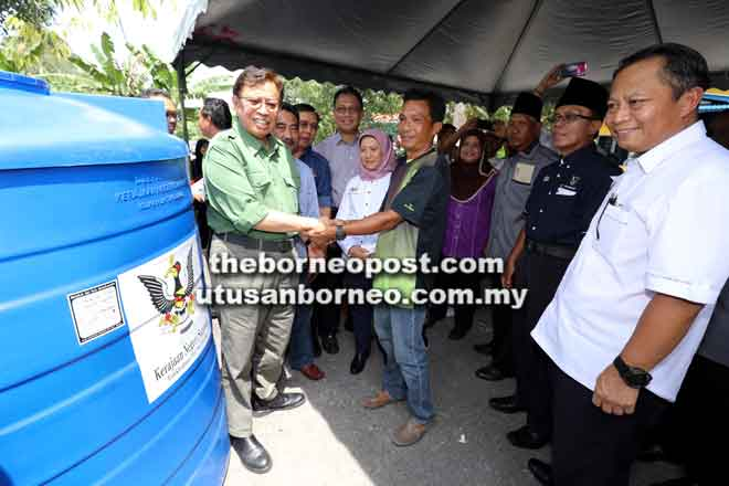 Abang Johari ditemani tetamu kehormat lain menyerahkan tangki air kepada penduduk Kampung Tanjung Kelaso, Sadong Jaya.