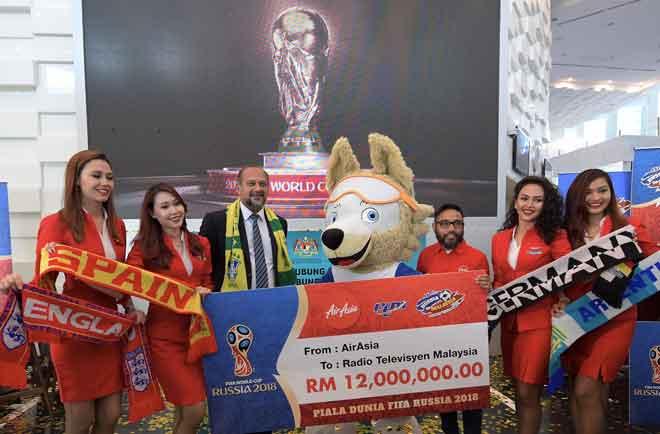 Gobind (tiga kiri) menerima replika cek sempena penajaan siaran langsung Piala Dunia FIFA 2018 daripada Riad (tiga kanan) bernilai RM12 juta pada majlis pelancaran dan sidang media 'FIFA World Cup Russia 2018' semalam. — Gambar Bernama