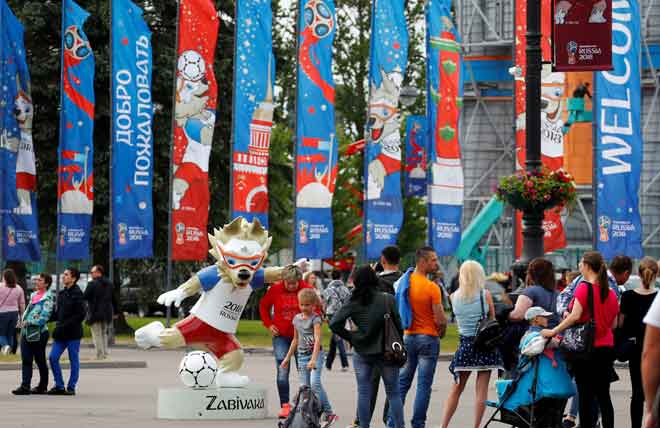 Orang ramai tertarik melihat maskot Piala Dunia 2018, Zabivaka yang di letakkan di laluan utama di Stadium Saint Petersburg, Rusia  kelmarin. — Gambar Reuters