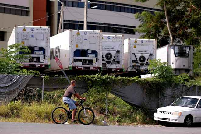 Seorang lelaki me-ngayuh basikal di hadapan kontena berhawa dingin mengandungi mayat tidak dituntut, diparkir di tempat letak kereta terbuka, bersebelahan Institut Forensik Puerto Rico di San Juan kelmarin. — Gambar AFP
