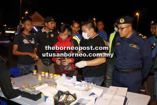 Syafiq (kanan) melihat anggota AADK melakukan ujian urin ke atas pengguna jalan raya.