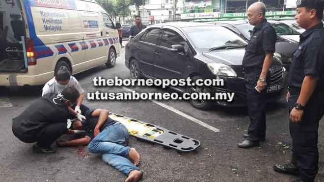 Lelaki warga Indonesia terbaring di atas jalan selepas terjatuh dari atas bangunan bilik sewa di Sibu pagi semalam.