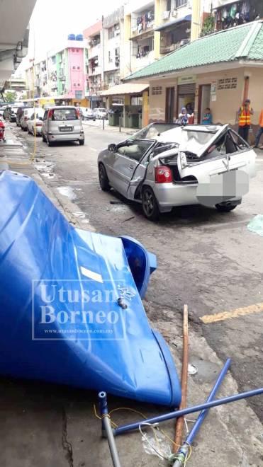 KEADAAN kereta yang rosak teruk selepas dihempap tangki yang jatuh dari tingkat satu bangunan.