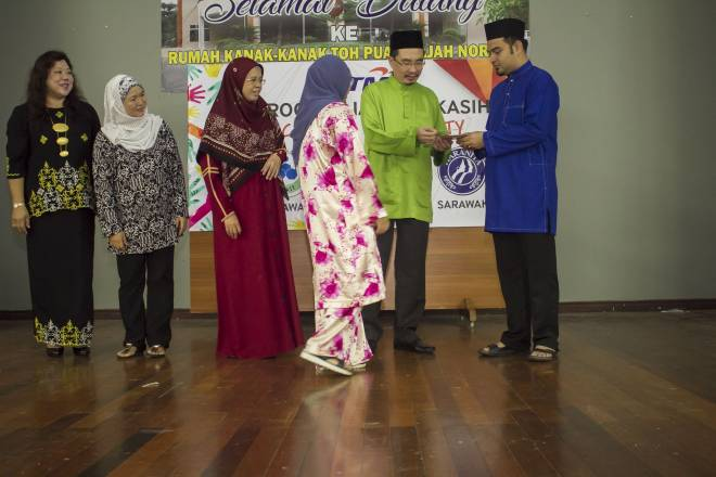 Jafer bersama Faeuziah menyerahkan sumbangan pada Majlis Berbuka Puasa di Rumah Kanak-Kanak Toh Puan Hajjah Norkiah  di Batu 12, Kuching, Sarawak.