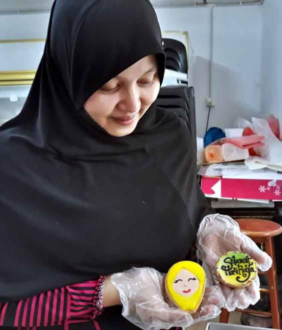 Noor Asmah menunjukkan 'fancy cookies' atau biskut yang mengandungi adunan nestum (di bahagian bawah) itu didekorasi (di bahagian atas) dengan 'royal icing' dengan tema pilihan berdasarkan permintaan pelanggan sempena sambutan Hari Raya Aidilfitri tidak lama lagi. — Gambar Bernama