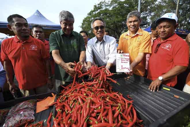 Ahmad (tengah) menunjukkan cili merah yang termasuk dalam harga kawalan selepas melancarkan Program Jualan Jimat Belanja sempena Hari Raya Aidilfitri di Pasar Tani Batu 4, Port Dickson semalam. — Gambar Bernama
