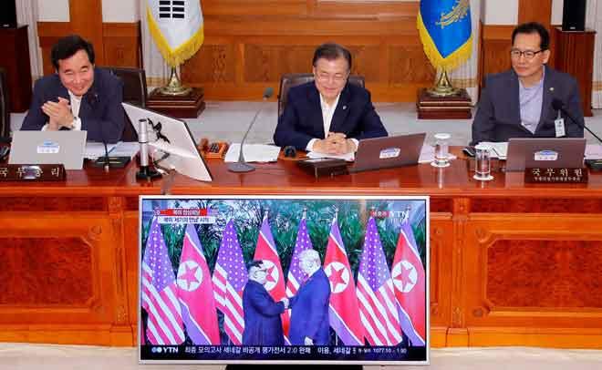Presiden Korea Selatan Moon Jae-in (tengah) menonton laporan berita televisyen mengenai sidang kemuncak bersejarah antara Trump dan Kim di Rumah Biru Presiden di Seoul, Korea Selatan kelmarin. — Gambar Yonhap/Reuters