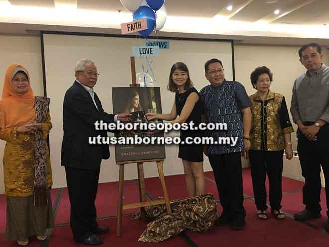 A Story of Hope, Courage, Strenght and Strenght' daripada Emelyne. Turut kelihatan Fatimah (kiri) dan Ahli Lembaga Dewan Bandaraya Kuching Utara Datuk Wee Hong Seng (tiga kanan).