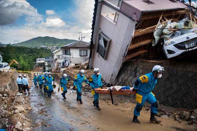 Anggota polis membantu dalam kerja membersihkan serpihan di jalan raya selepas banjir melanda kawasan kejiranan di Kumano, wilayah Hiroshima kelmarin. — Gambar AFP