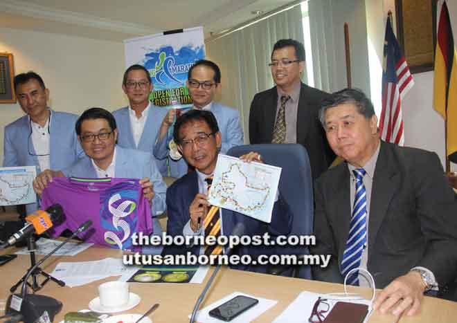 Abdul Karim (tengah) menunjukkan laluan KM2018 kepada media pada sidang media bersama Ong (kanan) dan Wong (kiri) di Kuching semalam.