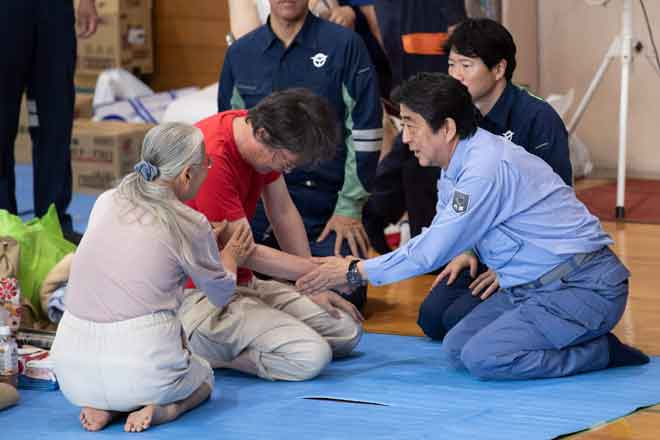 Abe (kanan) menenangkan salah seorang penduduk di pusat perlindungan sementara selepas bencana banjir                di Mabi, wilayah Okayama, Jepun semalam. — Gambar AFP