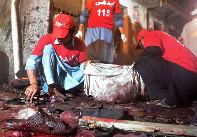Sukarelawan mengutip cebisan mayat selepas serangan bom nekad mengorbankan                        20 orang yang menghadiri perhimpunan pilihan raya di Peshawar, Pakistan kelmarin. — Gambar AFP
