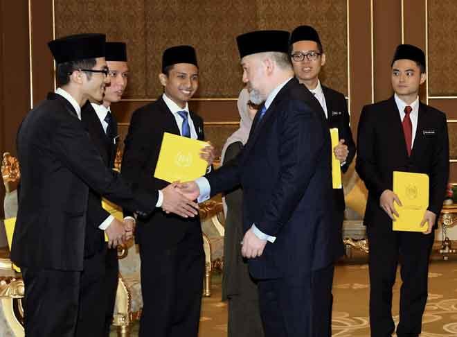 Sultan Muhammad V (tengah) berkenan beramah mesra bersama penerima Biasiswa Yang di-Pertuan Agong (dari kiri) Ng Wei Kuan, 24, Koh Kim Jie, 26, Raif Rafideen Norisman, 23, On Yue Yuan, 24, dan Yong Bang Xiang, 25, di Istana Negara di Kuala Lumpur, semalam. — Gambar Bernama