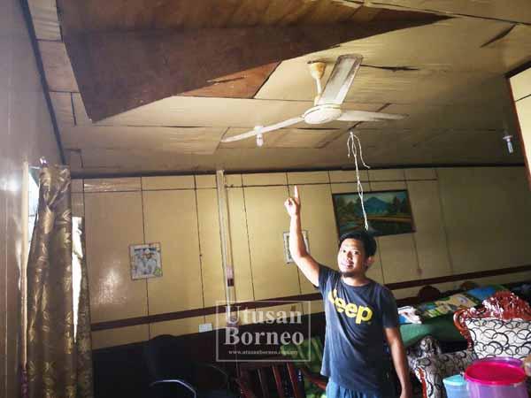 AGUSTRIONO menunjukkan siling rumahnya yang turut terjejas berikutan angin kencang yang melanda