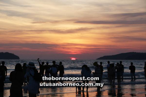 SUASANA pengunjung merakamkan detik matahari terbenam di Pantai Tanjung Aru.