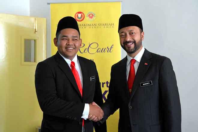 Mukhriz (kanan) bersalaman dengan Mohd Firdaus yang dilantik sebagai Pengerusi Jawatankuasa Penerangan, Komunikasi dan Multimedia, Badan-badan Bukan Kerajaan (NGO) Negeri Kedah di Alor Setar semalam. — Gambar Bernama