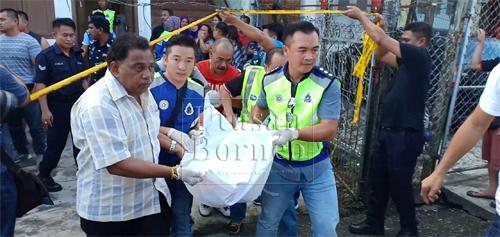 Mayat mangsa diangkat anggota polis untuk dibawa ke Hospital Sibu bagi bedah siasat