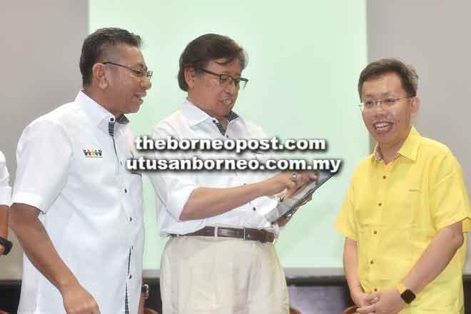 Abang Johari menekan butang pada tablet sebagai simbolik pelancaran Aplikasi Pelajar Yayasan Sarawak pada majlis penyampaian Hadiah Pelajar Cemerlang Aplikasi Pelajar Yayasan Sarawak sambil disaksikan Azmi (kiri) dan Menteri Kerajaan Tempatan dan Perumahan Datuk Dr Sim Kui Hian (kanan).