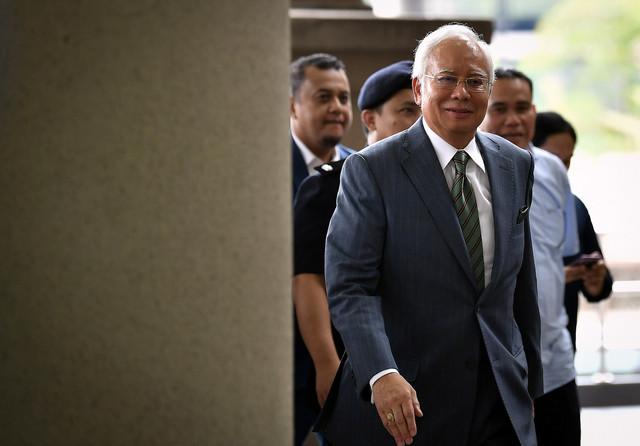 Najib diiringi oleh anggota polis ketika hadir untuk didakwa atas tiga pertuduhan menerima wang daripada aktiviti haram di Mahkamah Sesyen di Kompleks Mahkamah Kuala Lumpur hari ini. - Foto Bernama