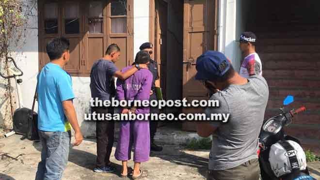 Suspek diiringi anggota polis ke tempat kejadian di rumah mangsa di Jalan Tiong Hua, Sibu pagi semalam.