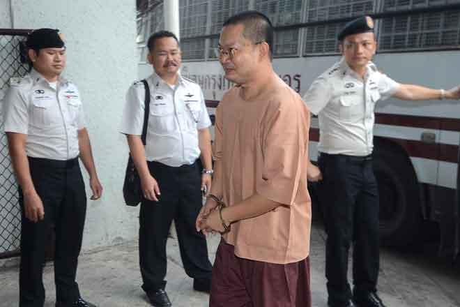 Anggota pasukan keselamatan berkawal ketika Wiraphon (bergari) tiba               untuk perbicaraannya di Mahkamah Jenayah di Bangkok, Thailand semalam. — Gambar Dailynews/Reuters