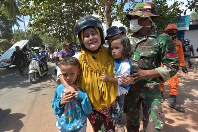 Seorang wanita menangis ketakutan sambil memeluk erat dua anaknya sejurus selepas gegaran susulan kuat melanda daerah Tanjung di utara Lombok semalam. — Gambar Adek Berry/AFP