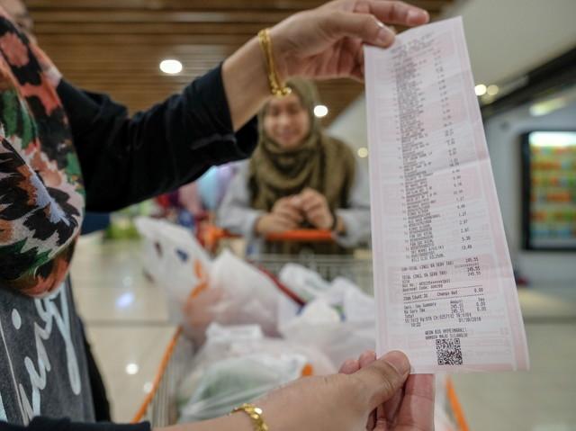 Seorang pelanggan Fariha Harun, 35, menunjukkan resit jualan yang dikenakan SST dengan kadar 6 peratus di sebuah pasaraya Wangsa Maju hari ini. - Gambar Bernama